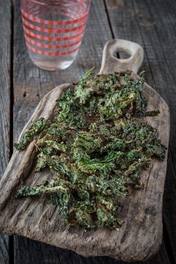 Eine Portion Grünkohlchips auf einem Holzbrettchen