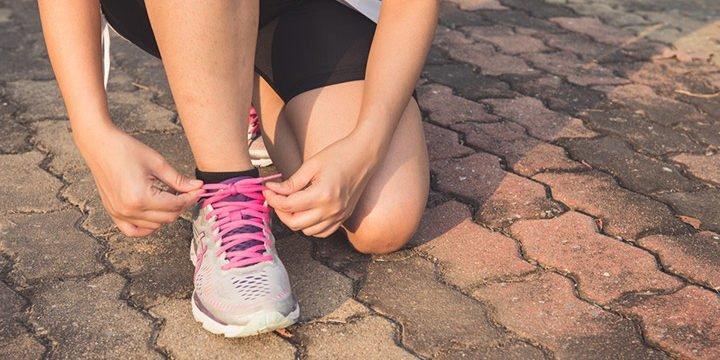 Eine Läuferin bindet sich die Schuhe