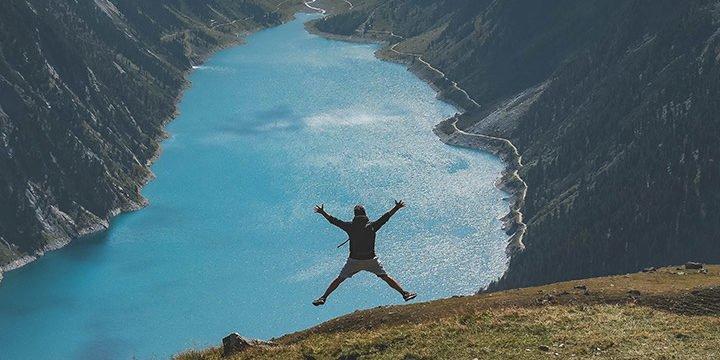 Ein Mann springt vor einem Bergsee