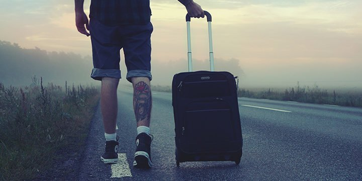 Ein Mann zieht einen Rollkoffer über eine Straße