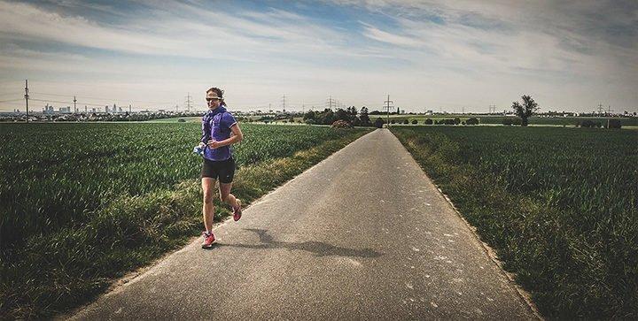 Katrin läuft auf einem Weg durch die Felder