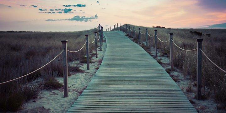 Ein Holzsteg am Strand bei Sonnenuntergang