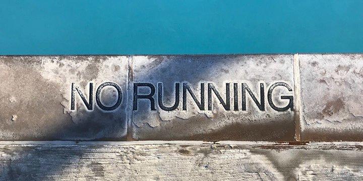 """Ein """"No Running"""" Schriftzug in einem Schwimmbad"""
