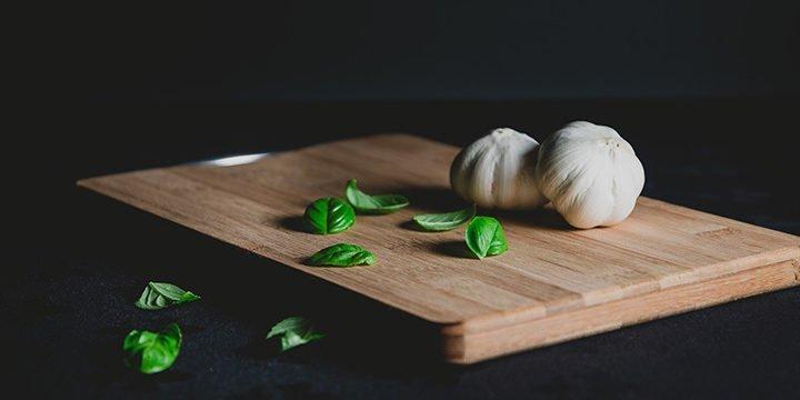 Ein Küchenbrett mit Knoblauchzehen und Basilikumblättern