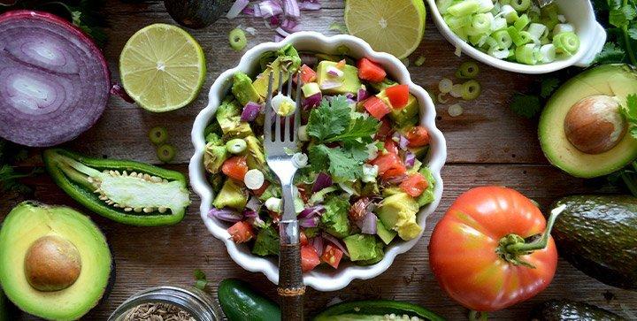 Titelbild: Eine Salatschale und verschiedene Gemüsesorten auf einer Tischplatte aus Holz