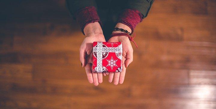 Zwei Hände halten ein kleines Weihnachtsgeschenk