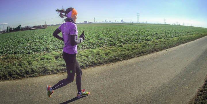 Titelbild: Katrin läuft auf einem asphaltierten Weg durch die Felder
