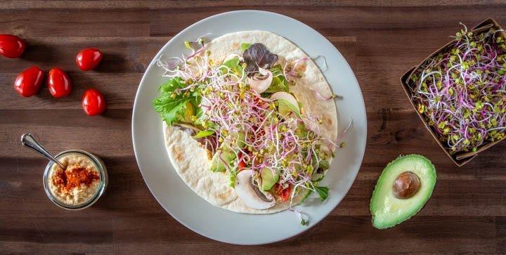 Ein veganer Wrap mit Hummus, Spinat, Tomaten, Avocado und Sprossen