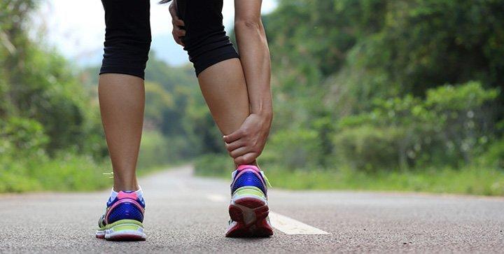 Eine Läuferin fasst sich an die Achillessehne