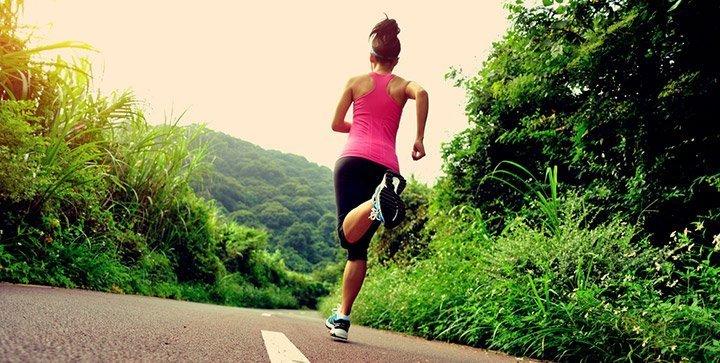 Eine Läuferin läuft auf einer Straße durch den Wald