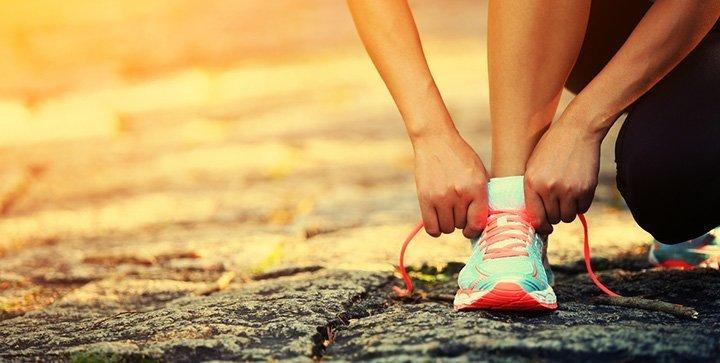 Eine Läuferin schnürt sich die Laufschuhe