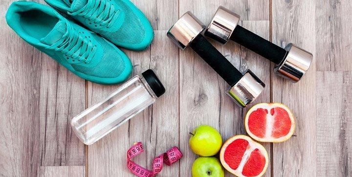Laufschuhe, Hanteln, Obst und ein Maßband