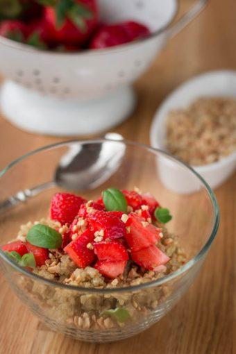 Eine Schale Quinoaporridge mit frischen Erdbeeren und gerösteten Mandeln