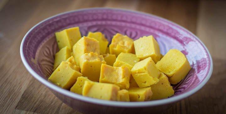 Eine Schale mit gelben Kichererbsen-Tofu-Würfeln
