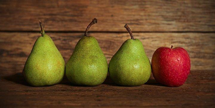 Drei Birnen und ein Apfel auf einem Holztisch
