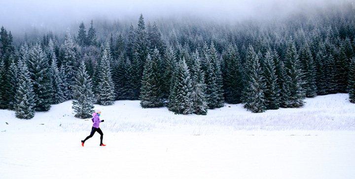 Eine Läuferin läuft durch eine Winterlandschaft
