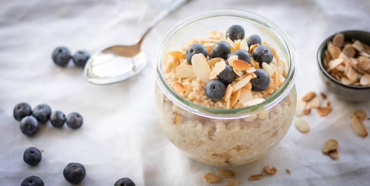 Porridge mit Mangostücken, Heidelbeeren und gerösteten Mandelblättern