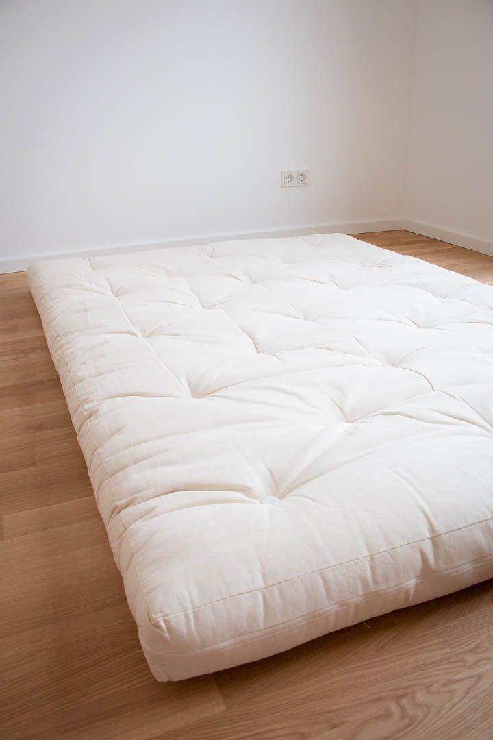 Ein weißer Futon liegt auf einem Parkettboden in einem leeren Raum