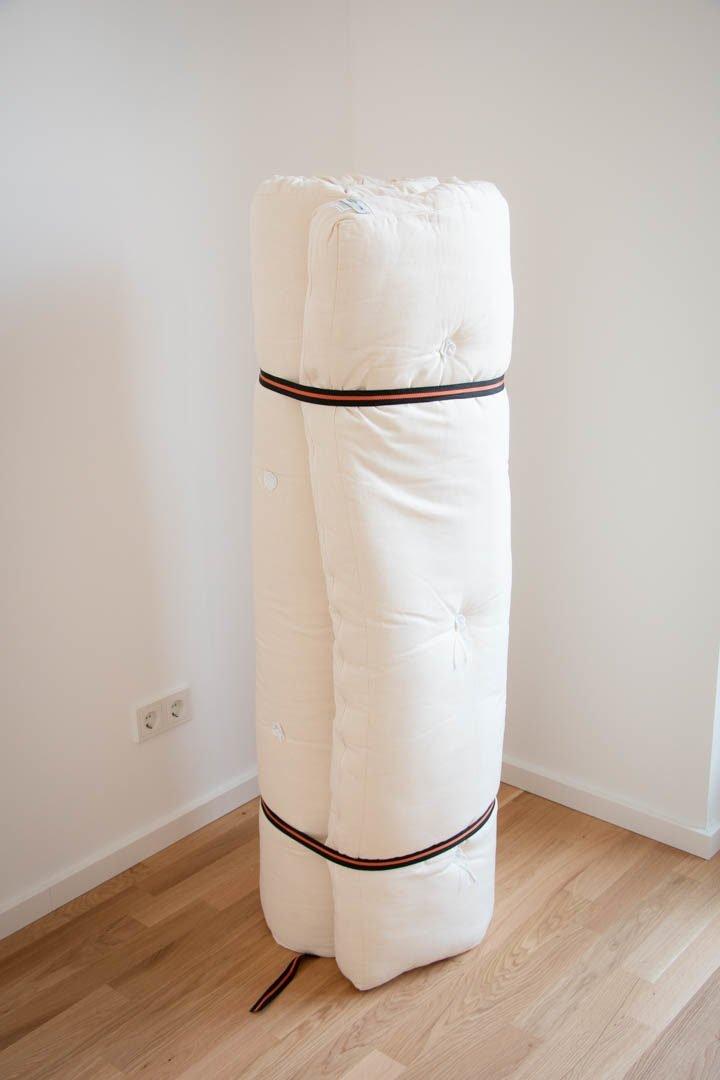 Ein zusammengerollter Futon steht in einer Zimmerecke
