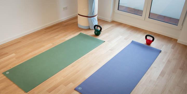 Zwei Yogamatten und zwei Kettlebells auf einem Parkettboden