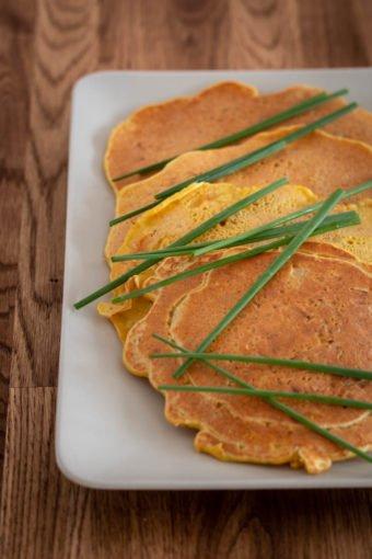 Vier Kichererbsenpfannkuchen mit frischem Schnittlauch liegen auf einem Teller