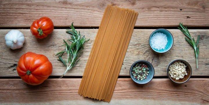 Verschiedene Pasta-Zutaten auf einem Holztisch: Tomaten, Knoblauch, Spaghetti, Salz, Pfeffer, Pinienkerne und Gewürze