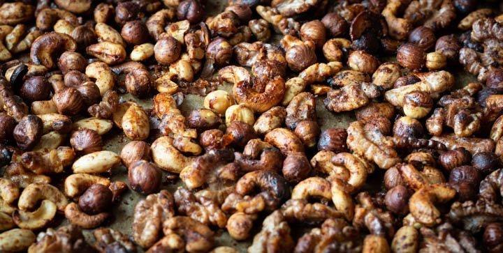 Titelbild: Geröstete Cashews, Haselnüsse, Walnüsse und Mandeln auf einem Backblech
