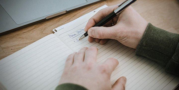 Titelbild: Eine Hand hält einen Kugelschreiber und notiert Vorsätze in ein Notizbuch