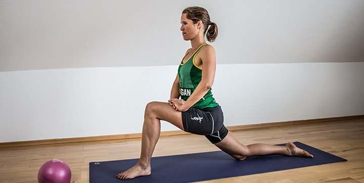 Katrin führt eine Stretchingübung auf einer Yogamatte durch