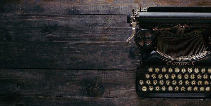 Eine schwarze Schreibmaschine steht auf einem Holztisch