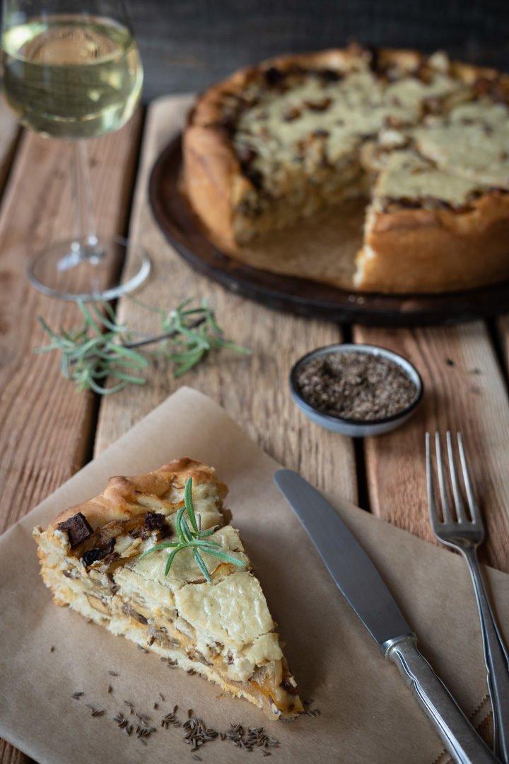 Ein Stück veganer Zwiebelkuchen mit Räuchertofu und Cashewsahne