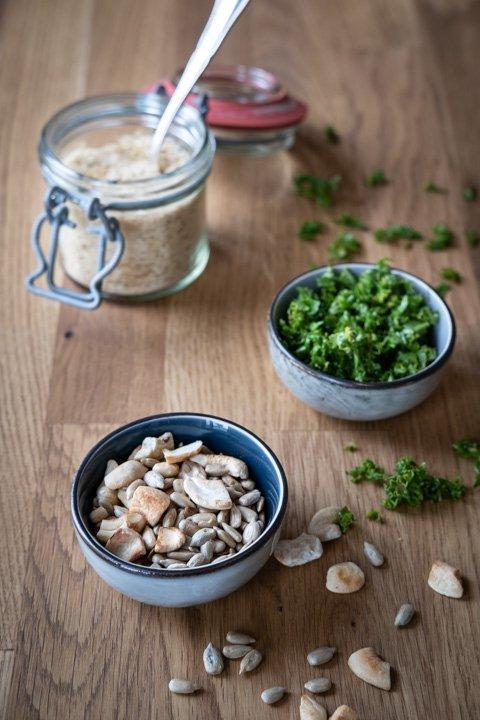 Drei Schälchen mit gerösteten Cashews, Petersilie und Hefeflocken