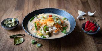 Ein Teller mit veganer Tom Ka Gai Suppe