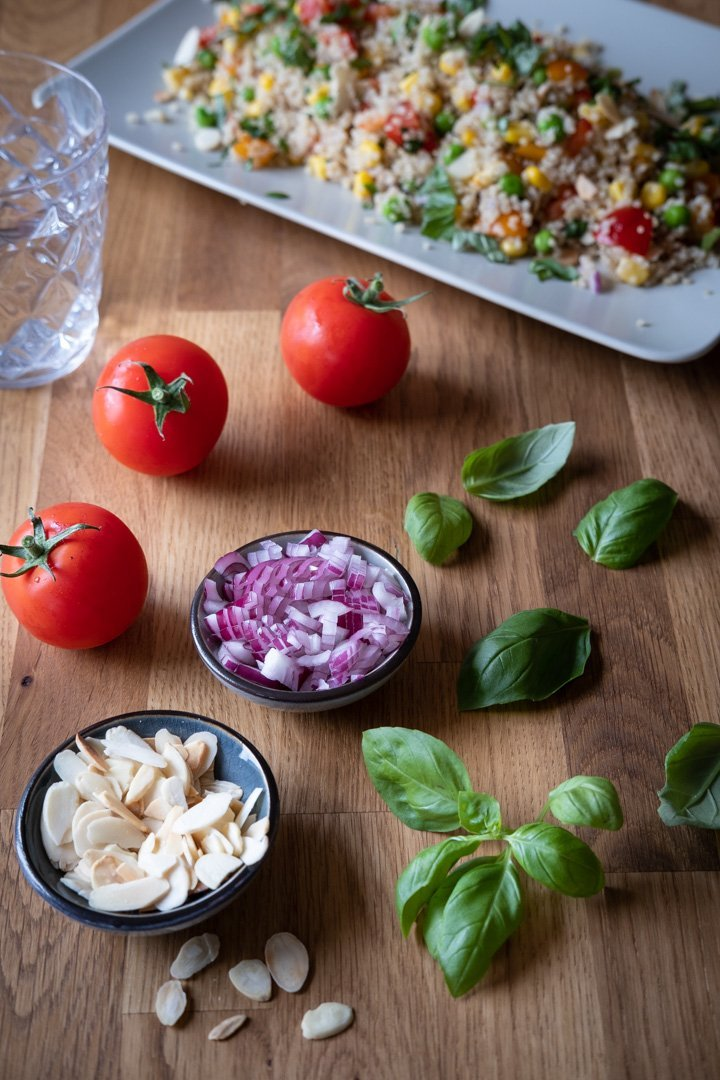 Zutaten für einen veganen Quinoasalat: Tomaten, Zwiebeln, Basilikum und Mandelblättchen