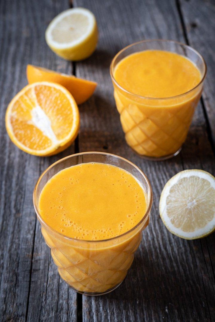 Zwei Gläser Orangen-Karotten-Zitronen-Saft mit Ingwer und Kurkuma