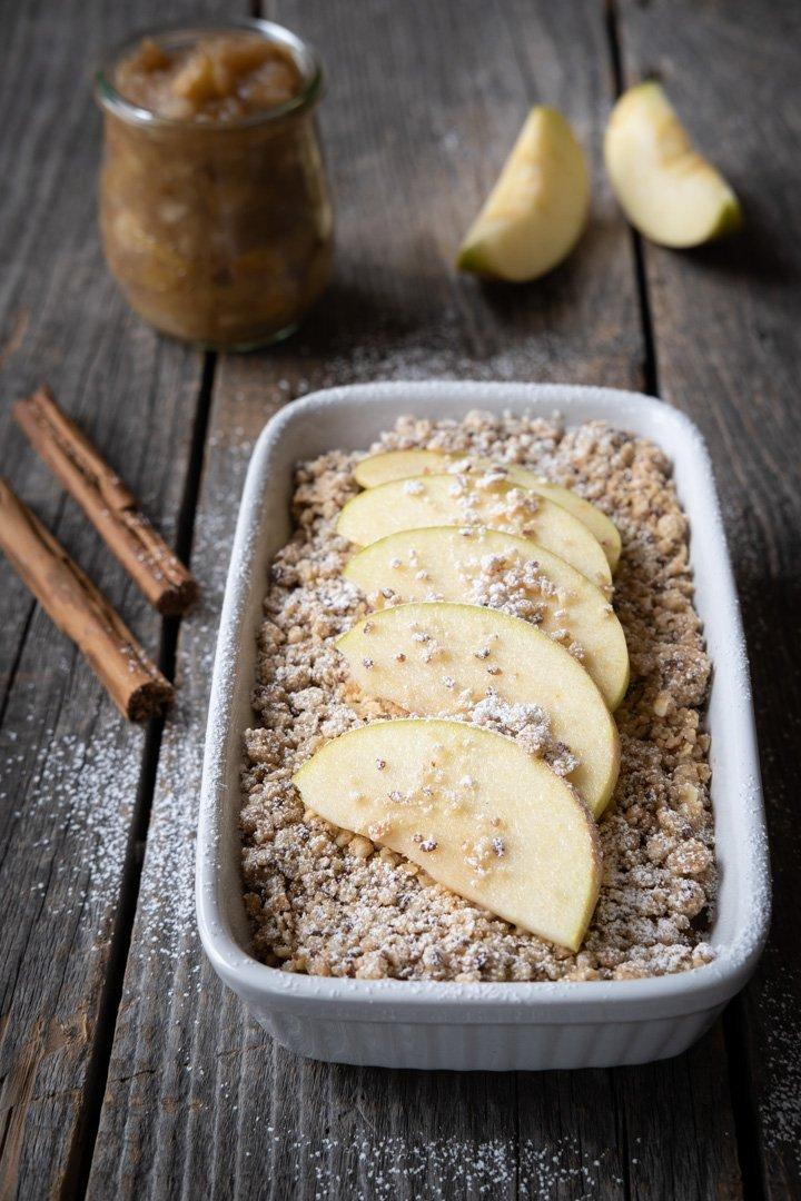 Ein veganer Apfel-Knusper-Crumble mit Zimtstangen und Apfelspalten