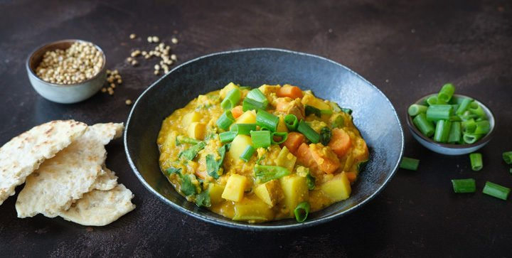 Titelbild: Ein Teller veganes Kartoffel-Linsen-Curry mit Pfannenbrot