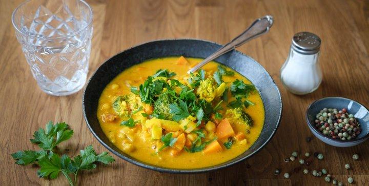 Ein Teller goldene Kichererbsensuppe mit Gemüse und Kurkuma
