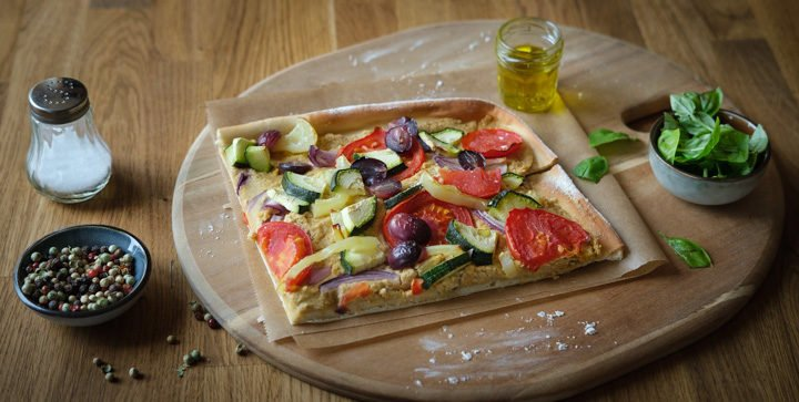 Ein Stück vegane Hummus-Pizza mit buntem Gemüsebelag